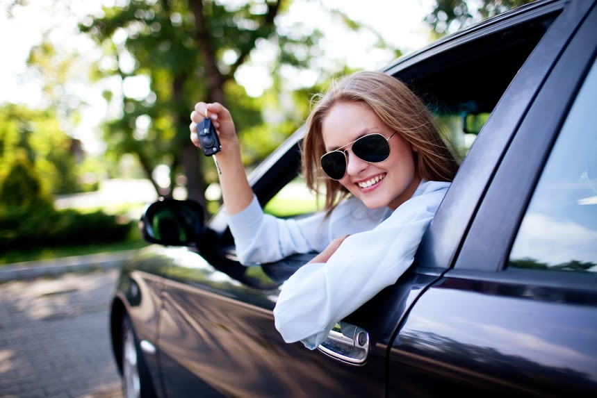 A girl leaning out a car window holding keys