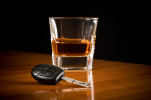 A shot glass next to a set of car keys