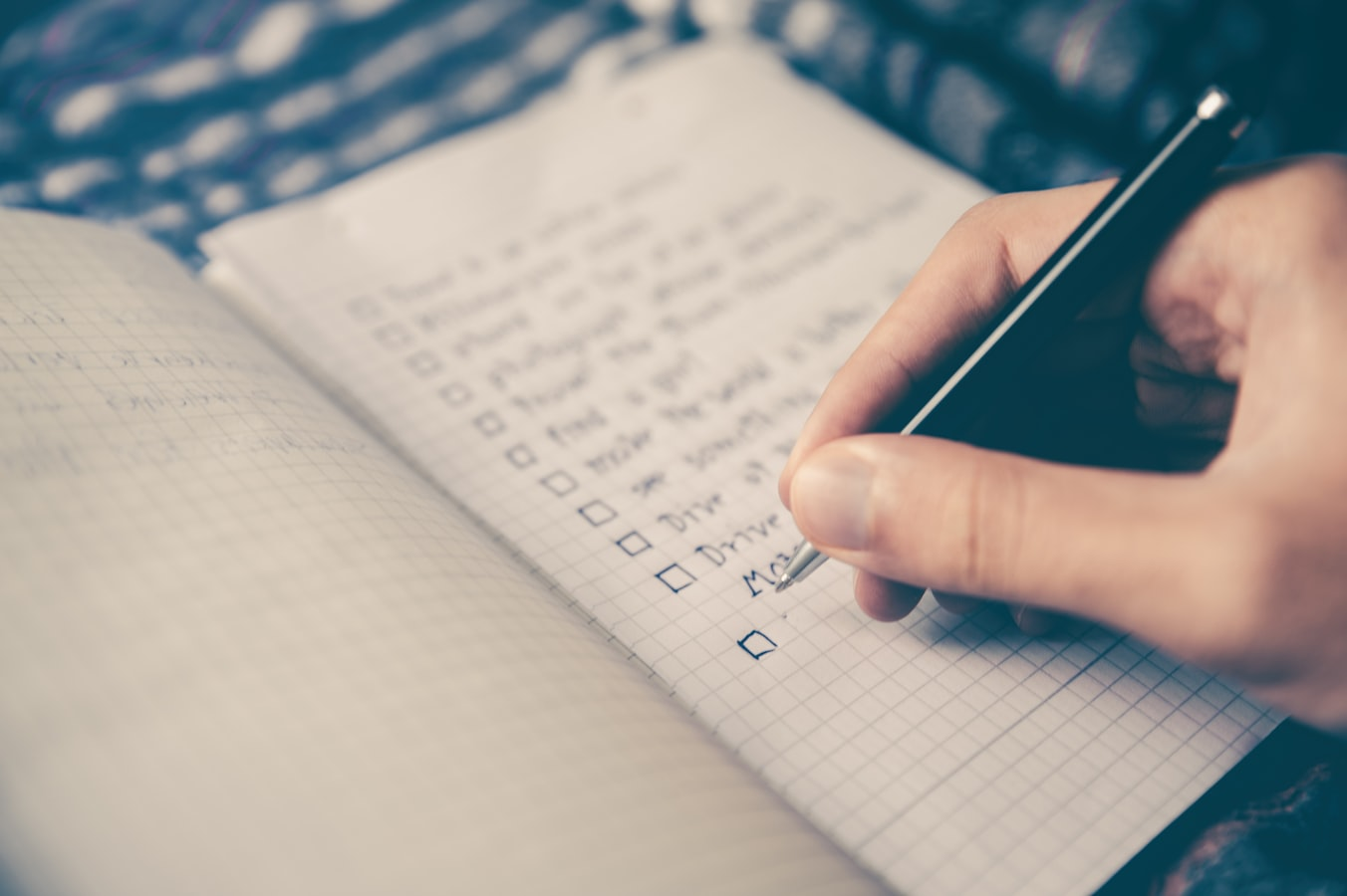 A person writing a checklist in a notebook
