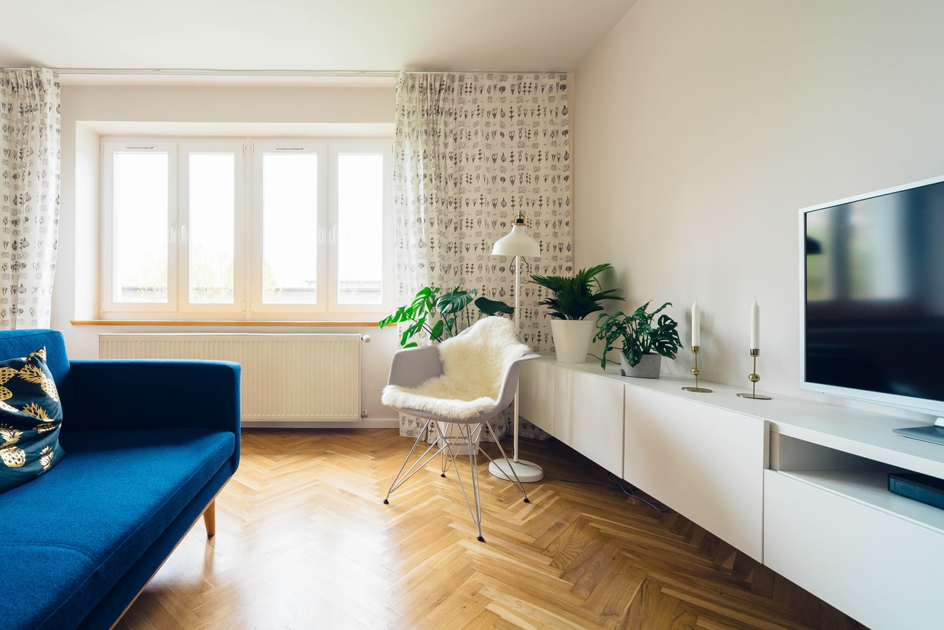 A small apartment with a blue sofa and big windows