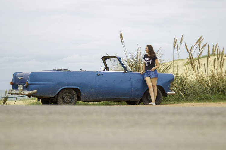 A woman standing on the side of the road next to a blue vintage vehicle