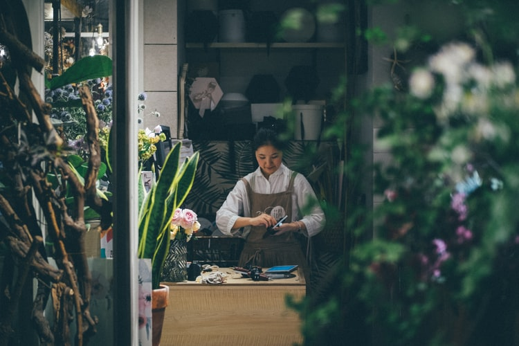 A woman working in a flower shop by herself